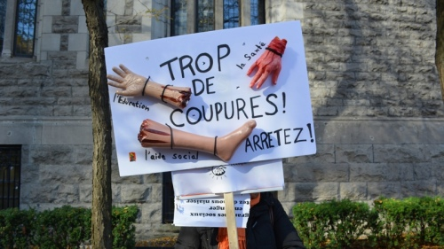 CANADA, MONTREAL: A woman holds a placard which reads: Education, health services, social help: Too many cuts! Stop!, on October 31, 2014.