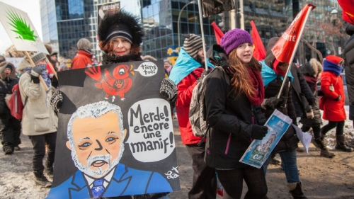 CANADA, Montreal: A woman holds a placard figuring Philippe Couillard that reads Merde! Encore une manif! during a demonstration against austerity in front of the HSBC office, in downtown Montreal on February 23, 2015. This demonstration is part a of a national week of actions to denounce the austerity measures of the Philippe Couillard's government. Both the demonstration and the week of actions are organized by the Coalition opposée à la tarification et à la privatisation des services publiques, which reunites over 80 groups (unions, women centers, student assocations, community groups...)