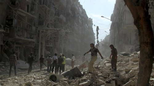 Residents and civil defense members look for survivors in a damaged site after what activists said was a barrel bomb dropped by forces loyal to Syria's president Bashar Al-Assad in Al-Shaar neighbourhood of Aleppo, Syria September 17, 2015. REUTERS/Abdalrhman Ismail